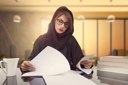 Donna di affari araba che rivede i risultati finanziari della società. documento di lettura sul posto di lavoro. Impiegato femminile soddisfatto con analisi di mercato, previsioni finanziarie Archivio Fotografico - 89340552
