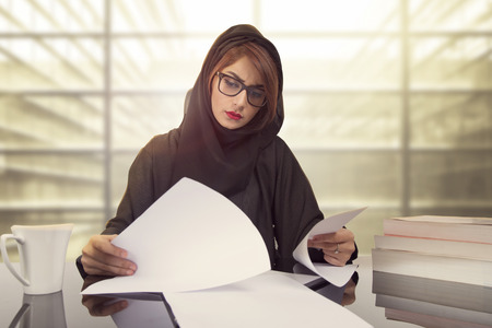 Arab businesswoman revising financial results. reading document at workplace. Female office worker satisfied with market analysis, financial forecast