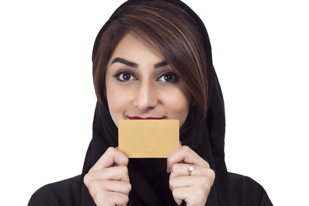 Arab Female holding golden card, focus on the debit card, over white background Imagens