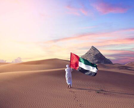 Emirati man holding UAE flag walking in the desert celebrate the national day - spirit of the union Stock Photo