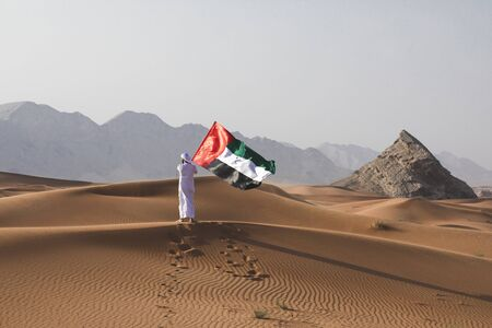 Arab man holding the UAE flag in the desert celebrating UAE national day and Uae flag day. Фото со стока