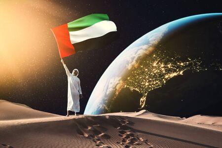 emirati man holding UAE flag standing on the moon 写真素材