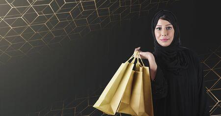 Arab woman holding golden luxurious shopping bags, standing on black background. Reklamní fotografie