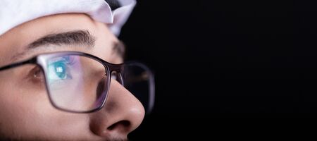 Focused and thoughtful Arab man in dark. macro of glasses of confident Arabic young male. isolated on black background.