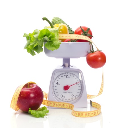 grow food: Healthy food on weights and measuring tape isolated on white