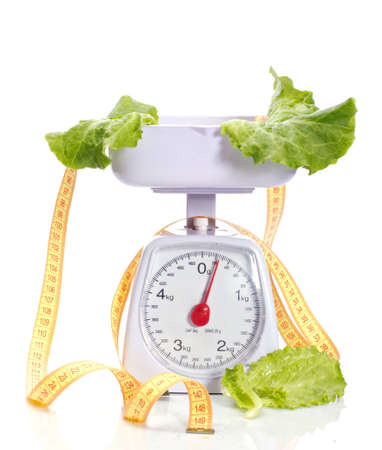 green salad on weights and measuring tape isolated on white photo