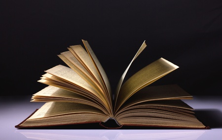 opened old book on black and white background