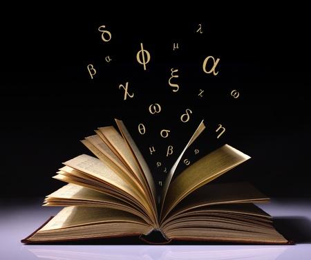 libros volando: libro abierto de edad con letras griegas volando sobre un fondo blanco y negro