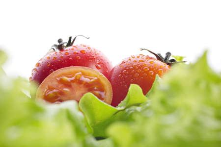 red tomatoes and green salad on white background