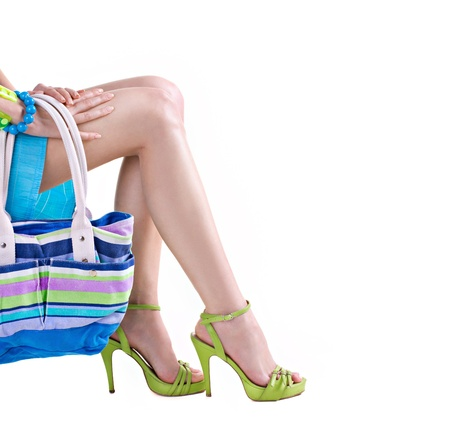 sexy womans legs in green shoes and handbag isolated on white