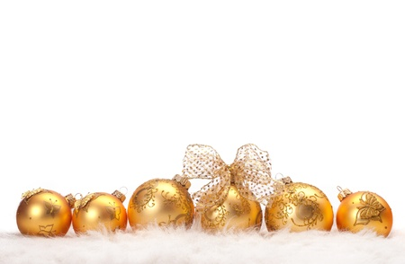 A row of gold Christmas balls in fur on white background photo
