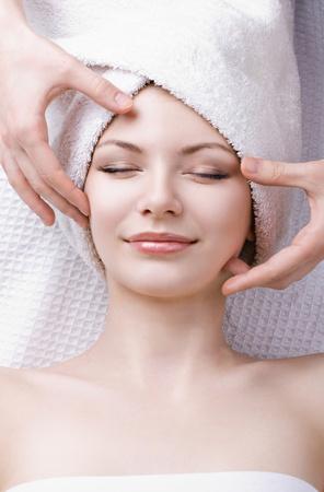 limpieza de cutis: hermosa mujer recibe masaje facial Foto de archivo
