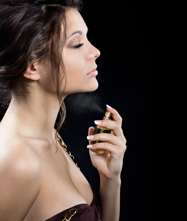 A portrait of a beautiful woman spraying perfume on black background