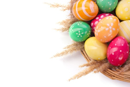 spring time: braided basket with Easter eggs isolated on white
