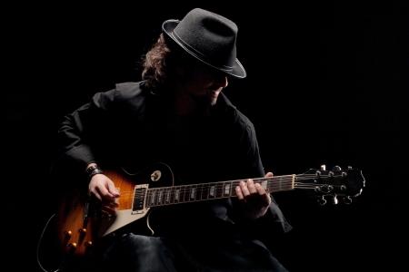 m�sico: Un hombre tocando la guitarra eletctric en ropas negras Foto de archivo