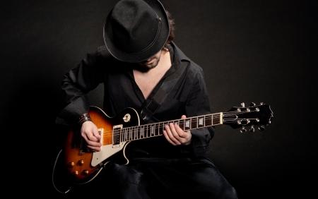 musicos: Un hombre tocando la guitarra eletctric en ropas negras Foto de archivo