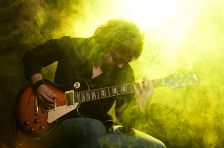 A man playing guitar sitting on a stage in yellow smoke