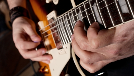 Close-up view of hands playing electric guitar