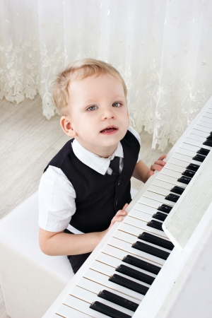 little kid near the piano in the room looking at camera photo