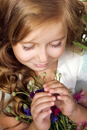 innocent girl: portrait of a little girl looking down with flowers