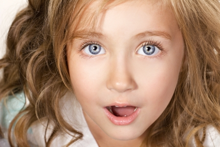 girl open mouth: close-up portrait of an amazed little girl with blue eyes