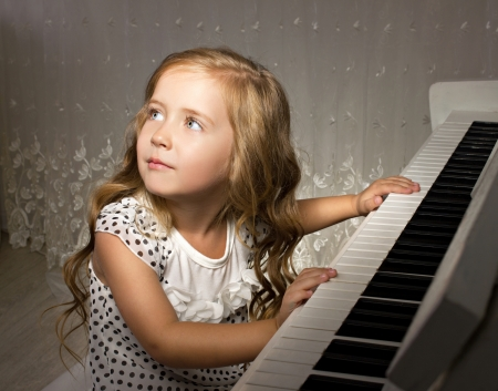 little girl playing piano in a white room photo