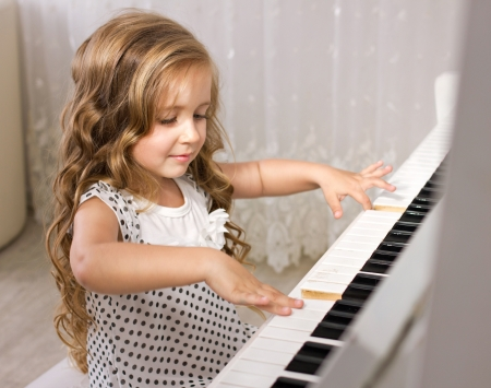 beautiful little girl playing piano in light room photo