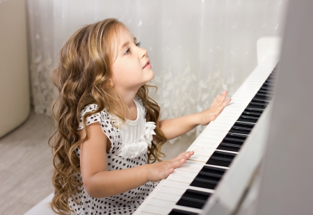 beautiful blond little girl playing near a piano in a white room photo