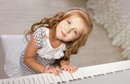 beautiful blond little girl with blue eyes in pretties sitting near a piano and  looking at camera photo