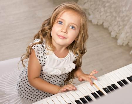 little girl playing piano looking at camera in light room photo