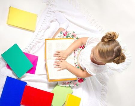 beautiful  little girl sitting among multicolored books on a white plaid and reading a book, top view photo
