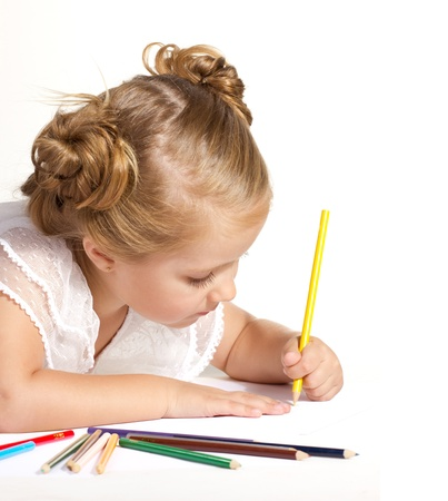 beautiful  little girl  drawing with colored pencils isolated on white photo