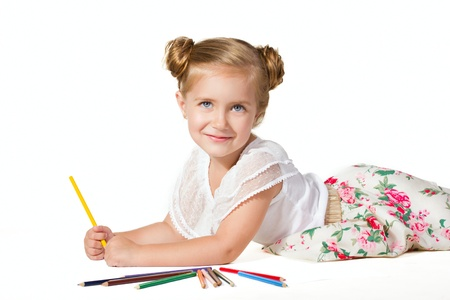 little girl lying and drawing with multicolored pencils isolated on white photo