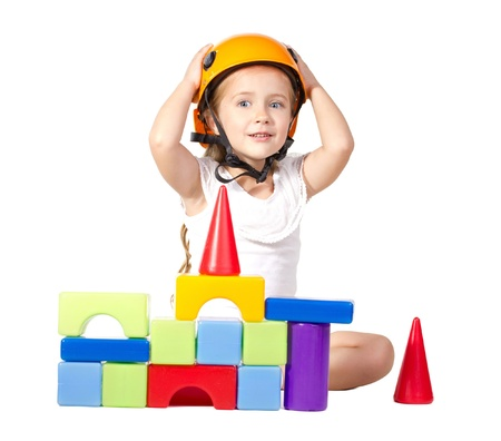 little girl  in helmet playing wiht blocks, looking at camera  isolated on white photo