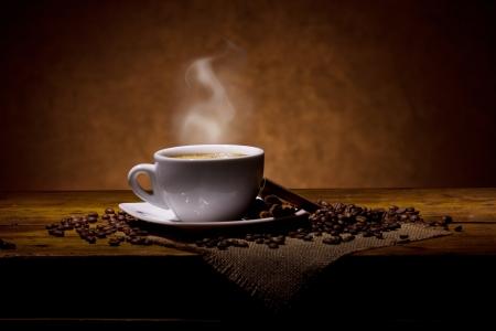 espressoo with smoke and cinnamon sticks on wooden table