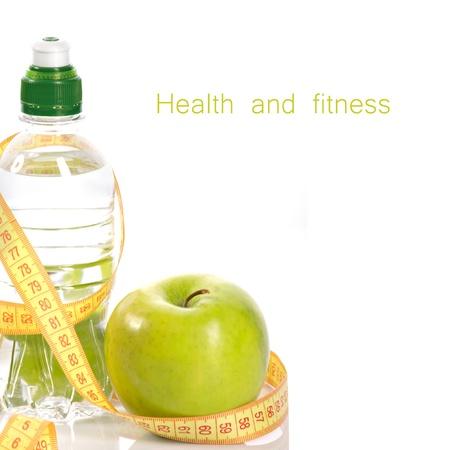 Green apple, bottle with aqua and measure isolated on white photo