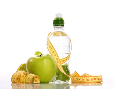 green apple, bottle with aqua,  small grapes and measure isolated on white photo