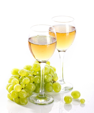 Two sweated wineglasses  with grapevine and bunch grape on white background photo