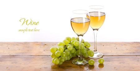racemation et deux verre de vin avec un liquide jaunâtre sur la table en bois, sur fond blanc