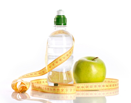 bottle with aqua, apple and measure on white background photo