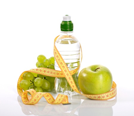 bottle with aqua, apple grapes, and measure on a white  background Stock Photo - 14990939