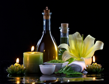 Spa oil, candles, flowers and spa cosmetics on black background photo