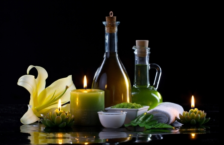 Spa oil, candles, flowers and treatment cosmetics on black background photo