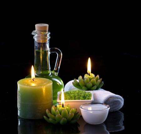 Spa oil, candles  and spa cosmetics on black background