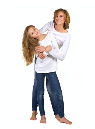 barefoot teens: Mother and daughter huggind each other isolated on white