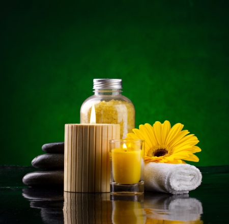 Spa still life with sea salts candles yellow flower and stones on green background