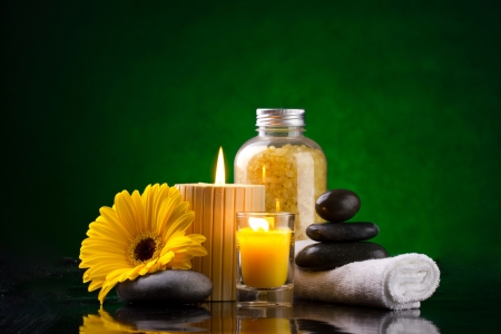 Spa still life with sea salts liting candles yellow flower white towel and stones on a green background photo