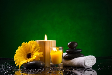 Spa still life with  candles flower towel and stones on green background