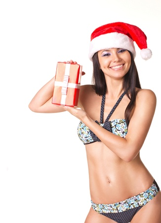 Beautiful  young woman  in Santa Claus  hat and swimsuit with gift  isolated on white