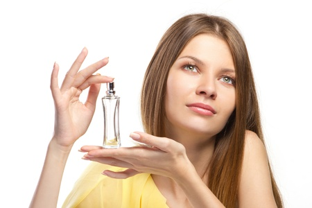 fragrant scents: beautiful aromatic  perfume in hands of young woman isolated on white